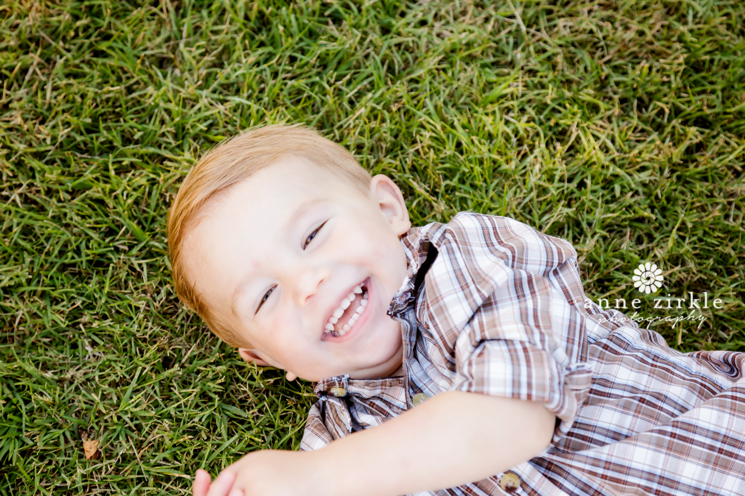 baby-boy-lying-in-grass-and-laughing