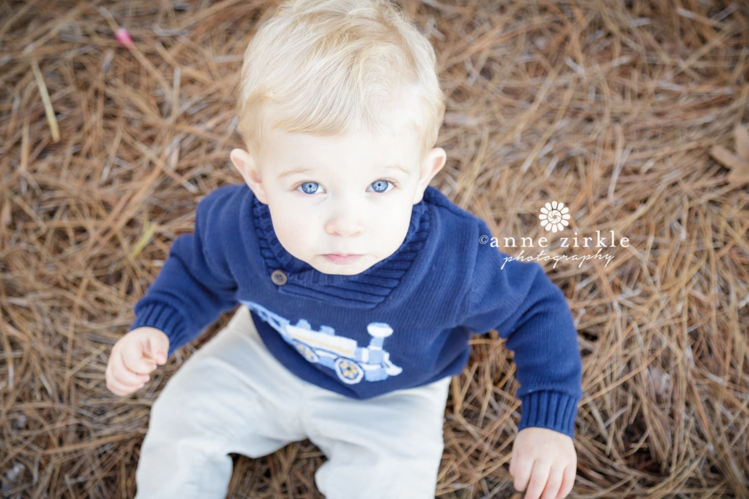 baby-boy-sitting-in-pine-straw-with-blue-eyes