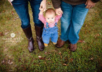baby-boy-standing-between-parents