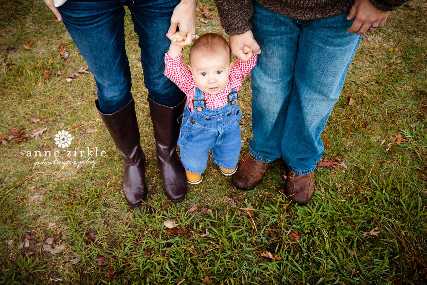 baby-boy-standing-between-parents