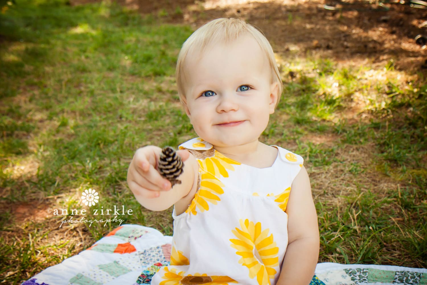 baby-girl-offering-a-pine-cone