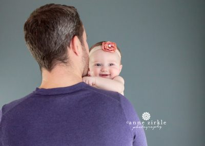 baby-girl-smiling-over-dads-shoulder