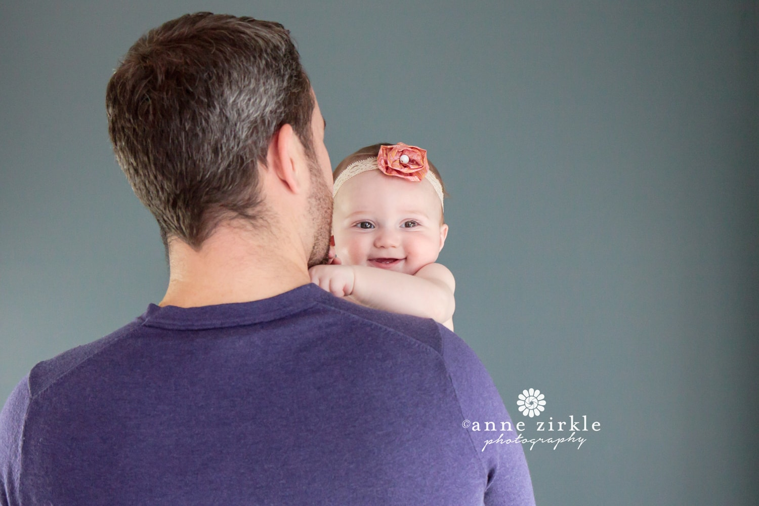 baby-girl-smiling-over-dads-shoulder