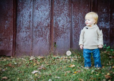 baby-standing-in-front-of-rusted-wall