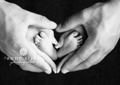 newborn-feet-held-in-parents-heart-shaped-hands