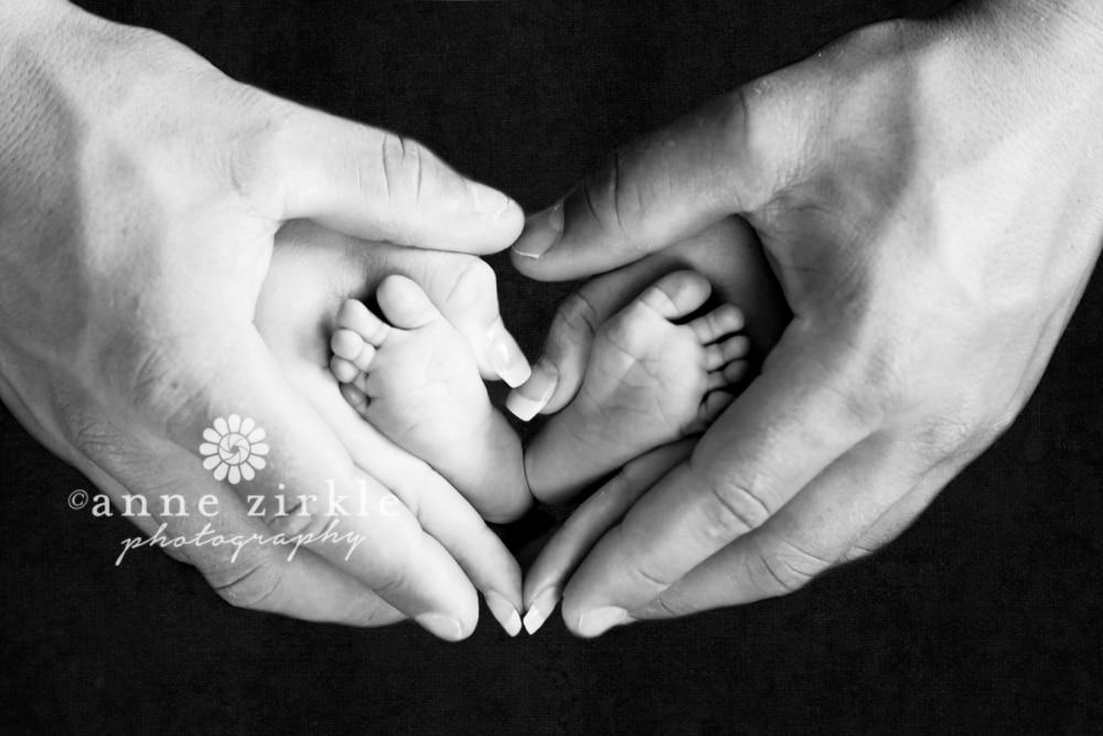 newborn-feet-held-in-parents-heart-shaped-hands