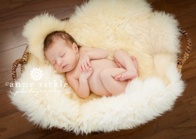 newborn-girl-sleeping-in-a-basket