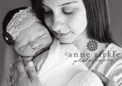 swaddled-newborn-girl-held-by-mother