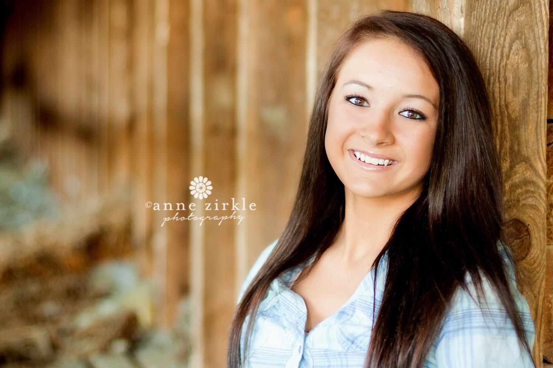teen-girl-leaning-on-barn-wall