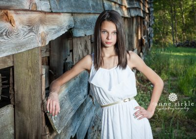 young-teen-girl-leaning-on-weathered-wood