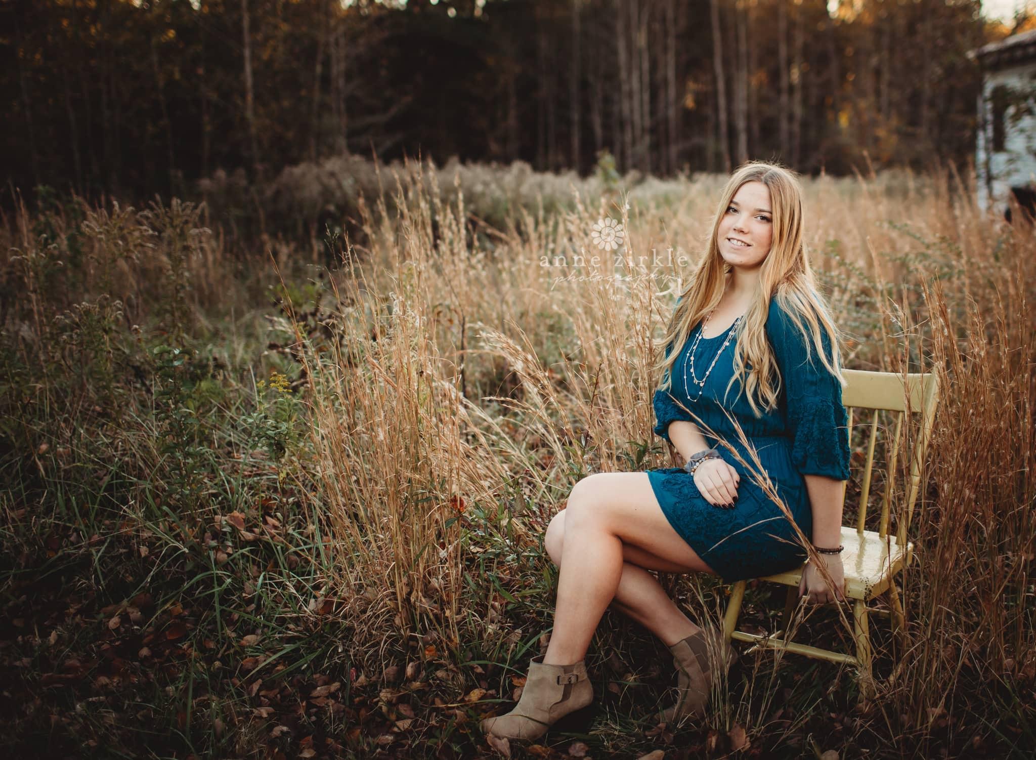 senior girl on a chair in autumn field