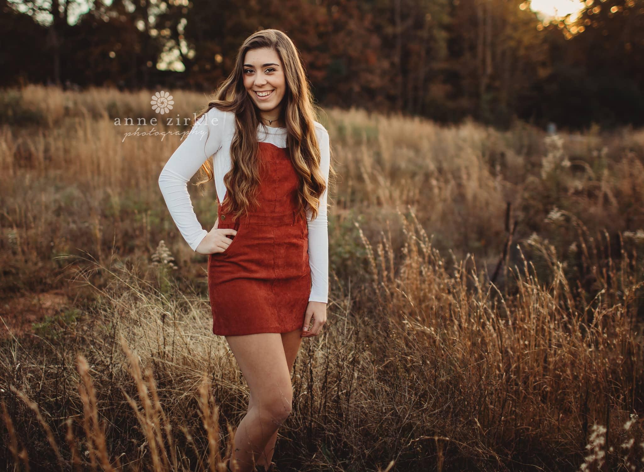 senior girl standing in autumn grasses