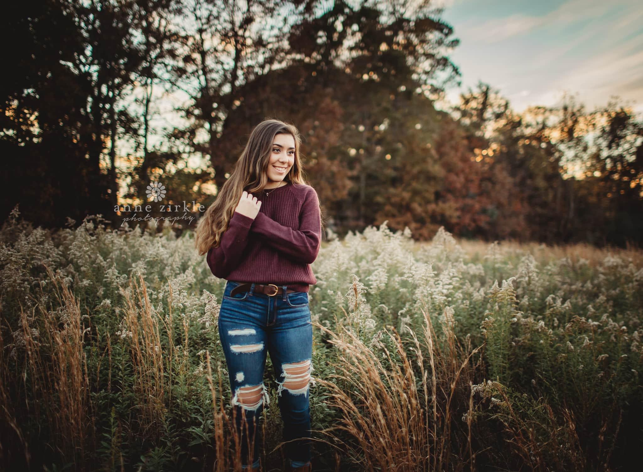 senior girl standing in wild flower field