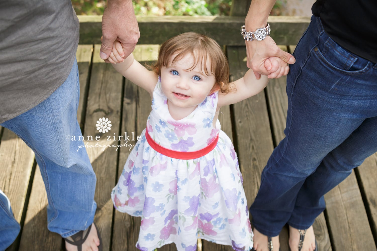 baby-girl-standing-between-parents