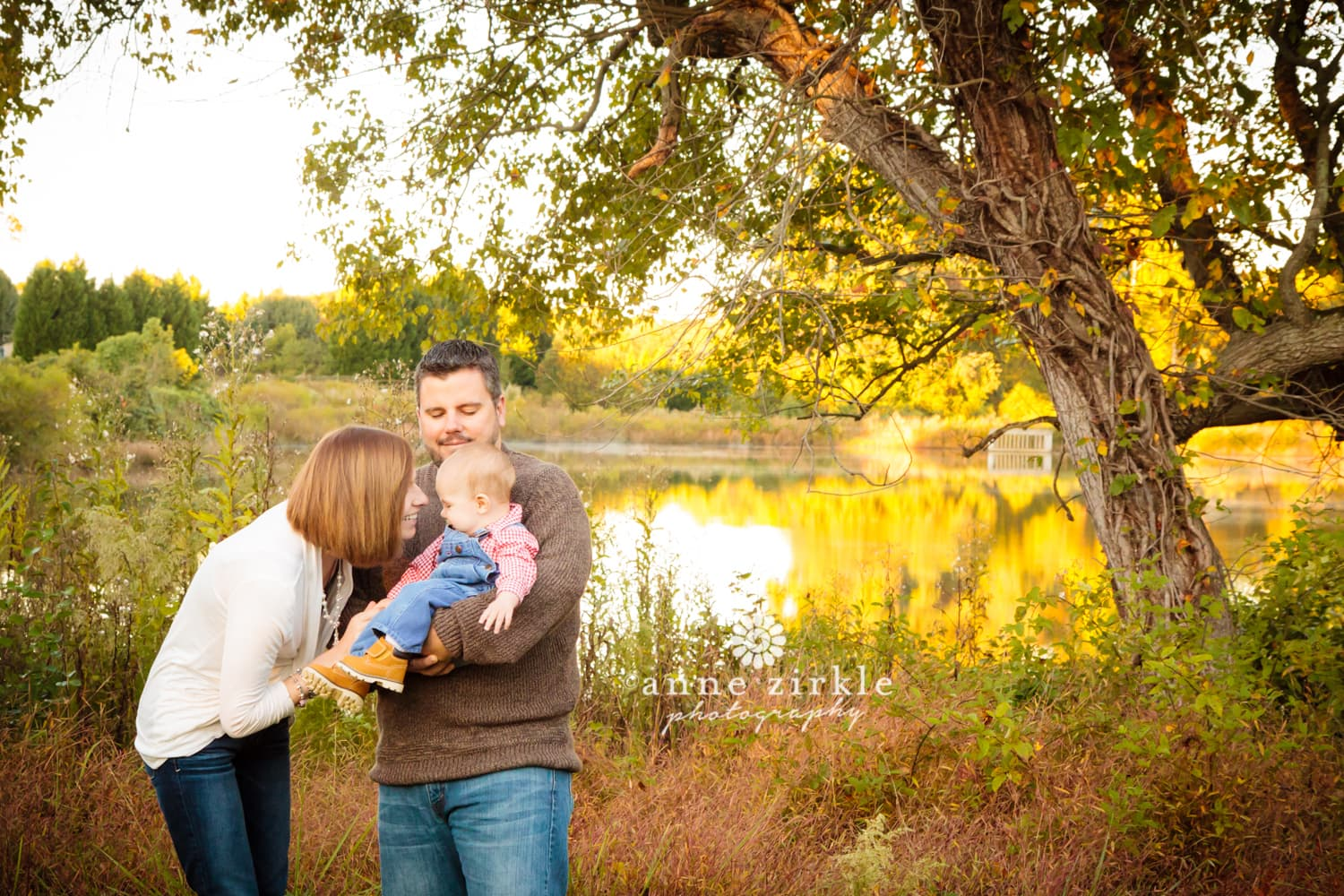 young-family-in-autumn-by-pond