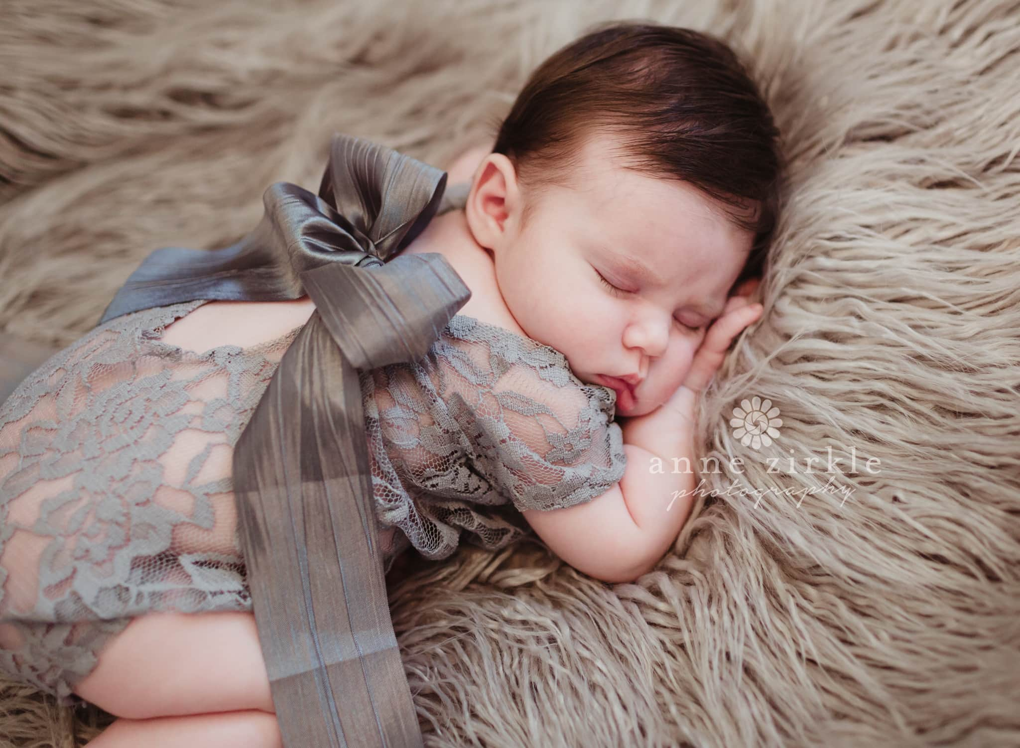 newborn girl in lace onesie with satin bow Mooresville and Lake Norman newborn baby photographer